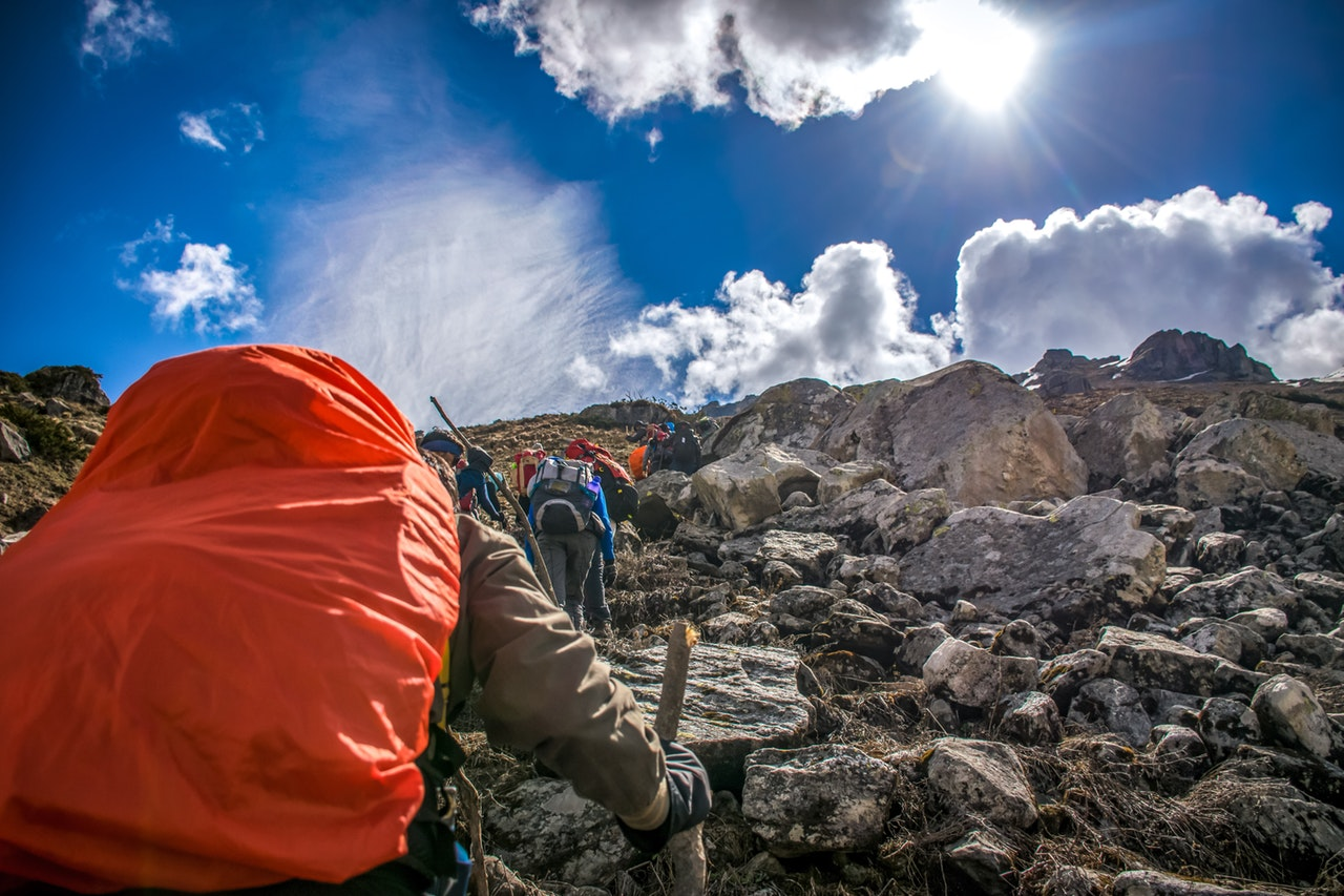 6 căi testate care te vor face să crezi în tine_om cu rucsac in spate care urca pe munte