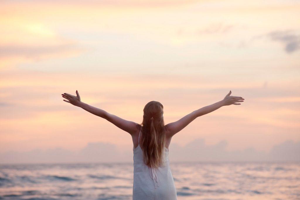 Femeie care este recunoscătoare la mare