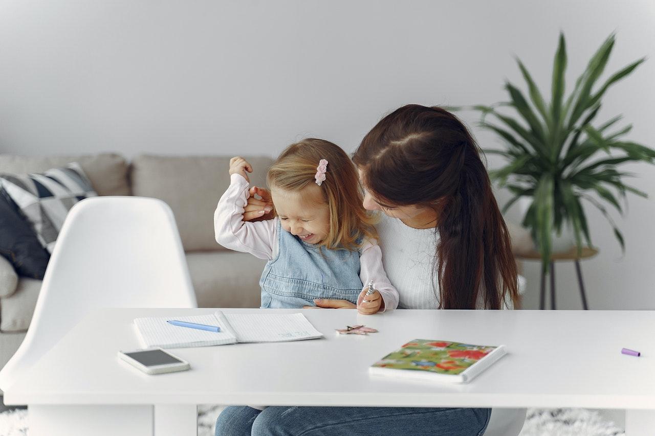 Cum-să-îți-adaptezi-rutinele-personale-și-cele-ale-familiei-la-noua-realitate_mama-și-fetița-scriu-la-masa